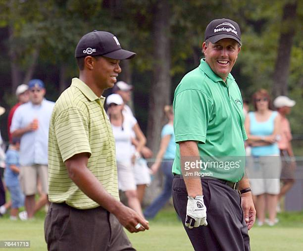 Phil Mickelson and Tiger Woods share a laugh during the first round of Deutsche Bank Championship, the second event of the new PGA TOUR Playoffs for...