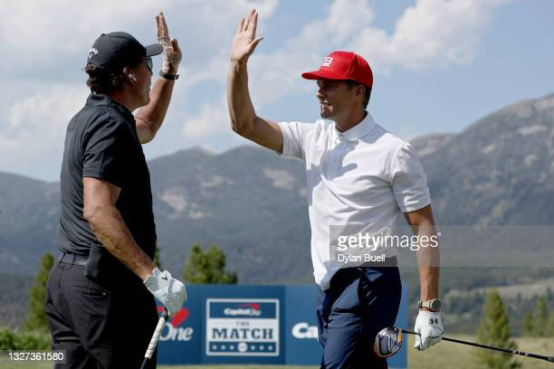 Phil Mickelson and Tom Brady high five on the third green during Capital One's The Match at The Reserve at Moonlight Basin on July 06, 2021 in Big...