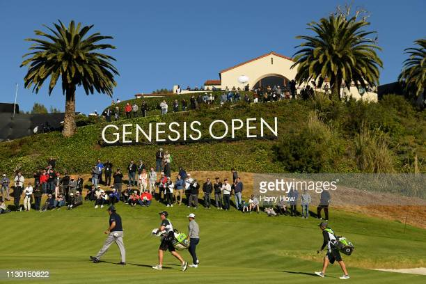 Phil Mickelson and Xander Schauffele walk up the 2nd hole green during the continuation of the second round of the Genesis Open at Riviera Country...