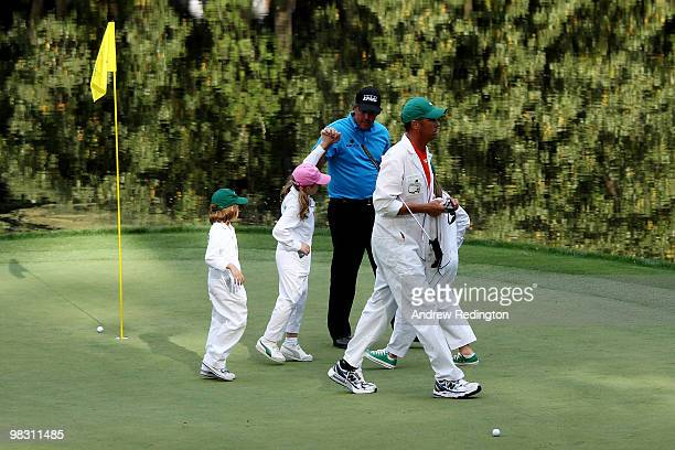 Phil Mickelson celebrates with his caddies/children Evan Sophia and Amanda as caddie Jim MacKay walks on during the Par 3 Contest prior to the 2010...