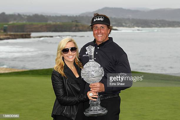 Phil Mickelson celebrates with his wife Amy while holding the tournament trophy after winning with an eightunderpar 64 during the ATT Pebble Beach...