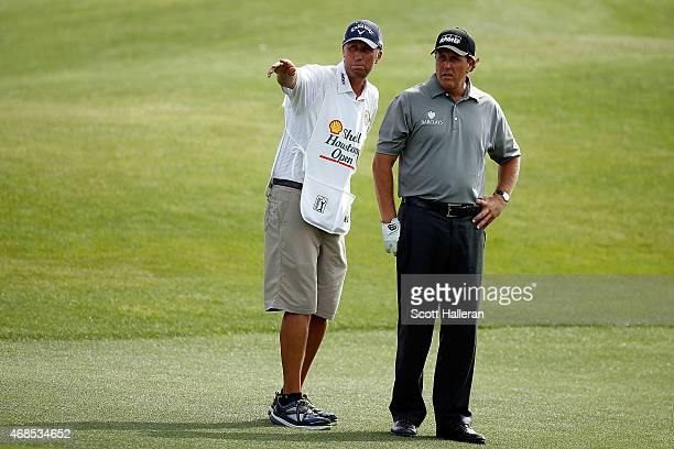 Phil Mickelson chats with his caddie Jim 'Bones' Mackay on the fifteenth hole during the second round of the Shell Houston Open at the Golf Club of...