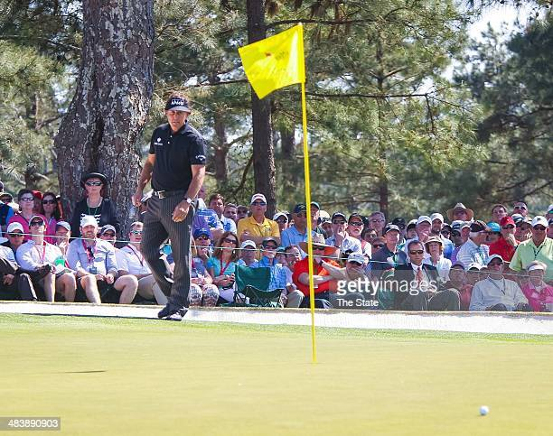 Phil Mickelson chips to the pin on the 7th green but the ball rolls past the hole and off the green during the first round of the Masters Tournament...
