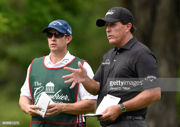 Phil Mickelson converses with his brother and caddie Tim on the 12th tee during round one of The Greenbrier Classic held at the Old White TPC on July...