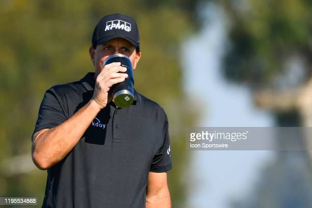 Phil Mickelson drink some coffee on the 1st hole on the South Course during the first round of the Farmers Insurance Open golf tournament at Torrey...