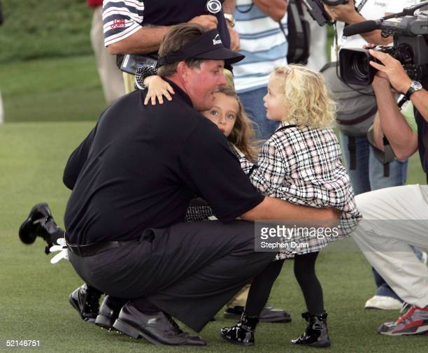 Phil Mickelson embraces daughters Amanda and Sophia after winning in the final round of the FBR Open on February 6 2005 at the Tournament Players...