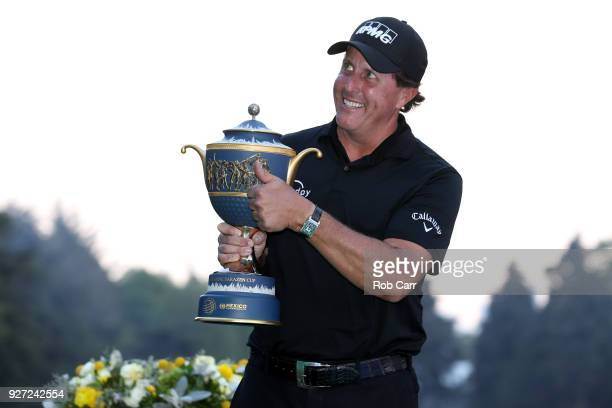Phil Mickelson gives a thumb up to fans as he holds the Gene Sarazen Cup after winning the World Golf Championships-Mexico Championship on a playoff...