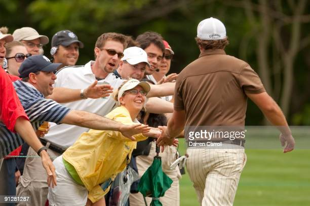 Phil Mickelson greets fans as he walks through the gallery during the continuation of the final round of the 109th US Open Championship on the Black...