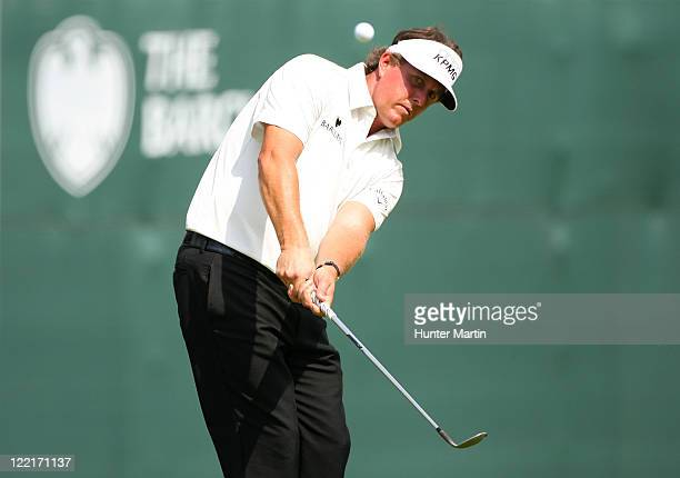 Phil Mickelson hits a chip shot onto the 18th hole green during round two of The Barclays at Plainfield Country Club on August 26 2011 in Edison New...