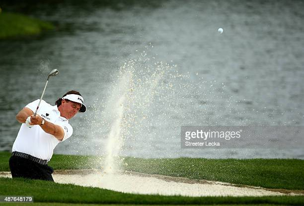 Phil Mickelson hits out of the sand on the 14th hole during the first round of the Wells Fargo Championship at Quail Hollow Club on May 1, 2014 in...