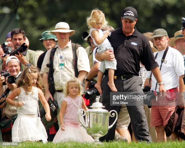 Phil Mickelson holds his daughter Evan as his other daughters Amanda and Sophia walk beside him in front of the Wanamaker Trophy after Mickelson won...
