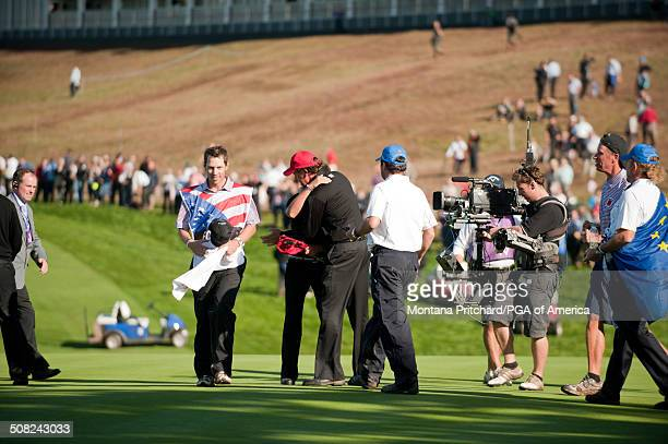 Phil Mickelson hugs Rickie Fowler during the session four singles matches at the 38th Ryder Cup at the Twenty Ten Course at Celtic Manor in Newport...