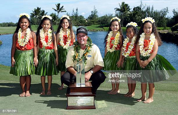 Phil Mickelson is pictured with the winner's trophy and six Keiki hula dancers after winning the 22nd PGA Grand Slam of Golf on November 24 2004 at...