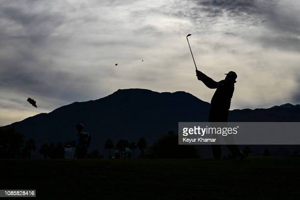 Phil Mickelson is silhouetted against the mountains as he hits his second shot on the 14th hole during the final round of the Desert Classic on the...