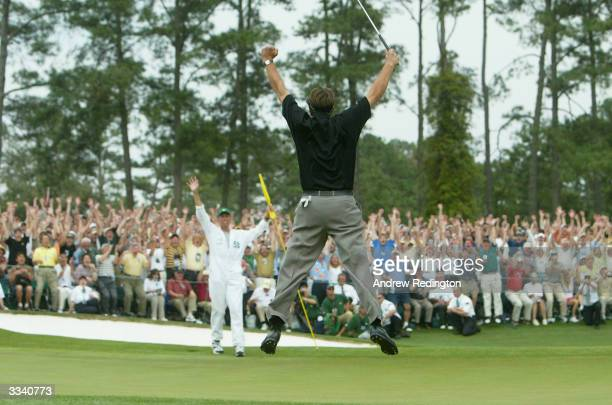 Phil Mickelson jumps in the air after sinking his birdie putt to win the Masters by one shot on the 18th green during the final round of the Masters...