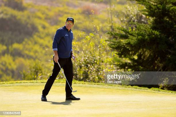 Phil Mickelson looks over his putt on the 15th green on the North course during the first round of the Farmers Insurance Open at Torrey Pines on...