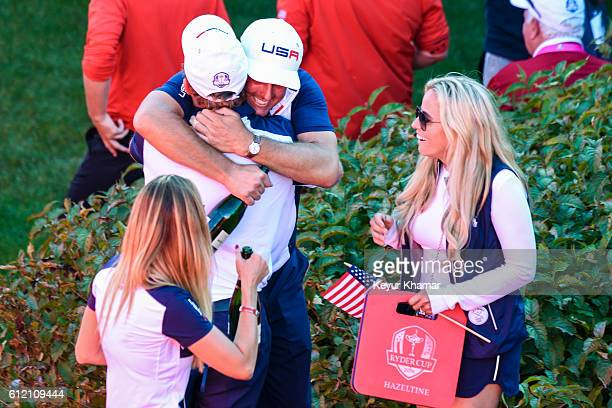Phil Mickelson of Team USA celebrates and hugs JB Holmes as his wife Amy Mickelson watches following the team's victory during singles matches of the...