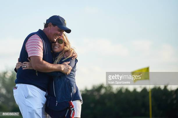 Phil Mickelson of the American Team embraces his wife Amy on the 18th green during the second round of the Presidents Cup at Liberty National Golf...
