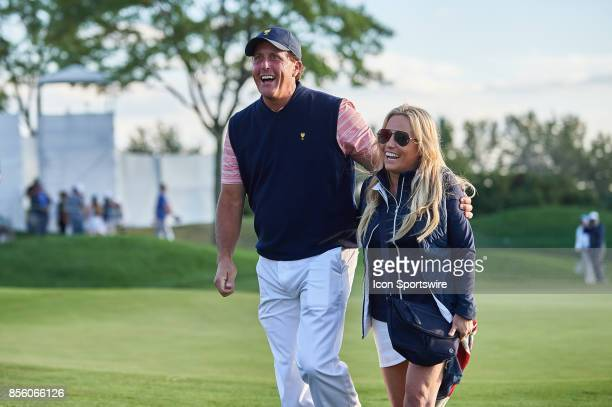 Phil Mickelson of the American Team smiles and walks with his wife Amy on the 18th green during the second round of the Presidents Cup at Liberty...