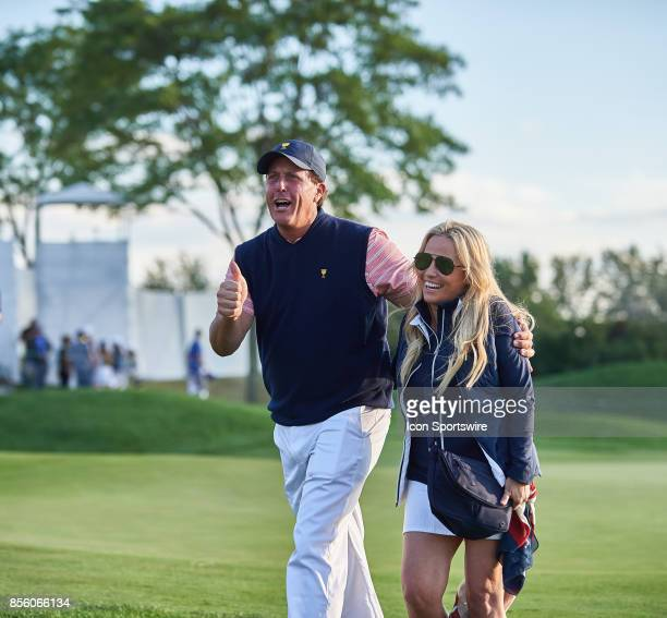 Phil Mickelson of the American Team smiles and walks with his wife Amy while giving a thumbsup to his fans on the 18th green during the second round...
