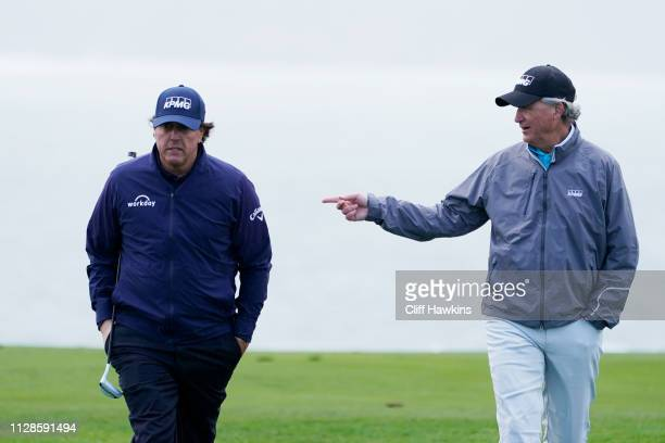 Phil Mickelson of the United States and Scott Ozanus Deputy Chairman and Chief Operating Officer of KPMG walk on the eighth hole during the third...
