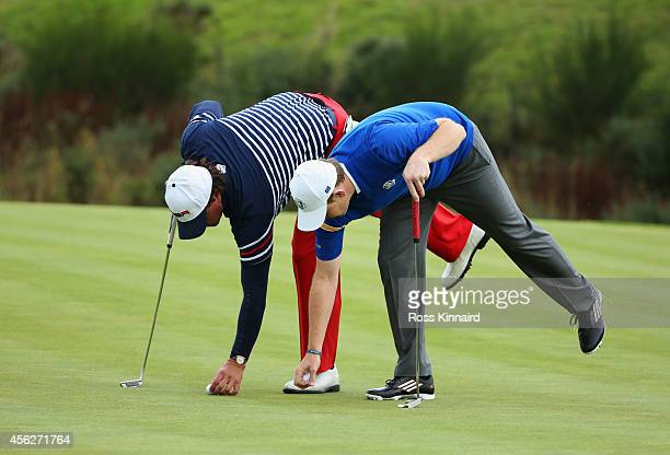 Phil Mickelson of the United States and Stephen Gallacher of Europe mark their balls on the 15th green during the Singles Matches of the 2014 Ryder...
