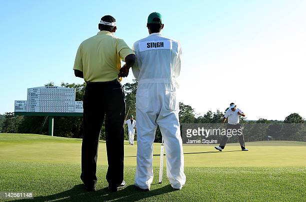 Phil Mickelson of the United States celebrates after making a birdie putt on the 18th hole as Vijay Singh of Fiji and his caddie Qass Singh look on...