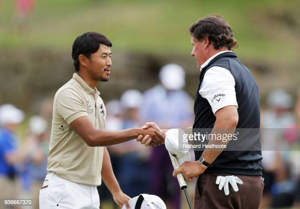 Phil Mickelson of the United States celebrates shakes hands with Satoshi Kodaira of Japan after defeating him 1up on the 18th green during the second...