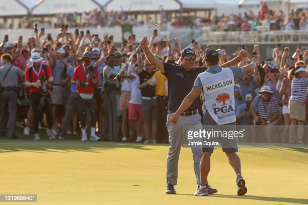 Phil Mickelson of the United States celebrates with brother and caddie Tim Mickelson after winning on the 18th green during the final round of the...