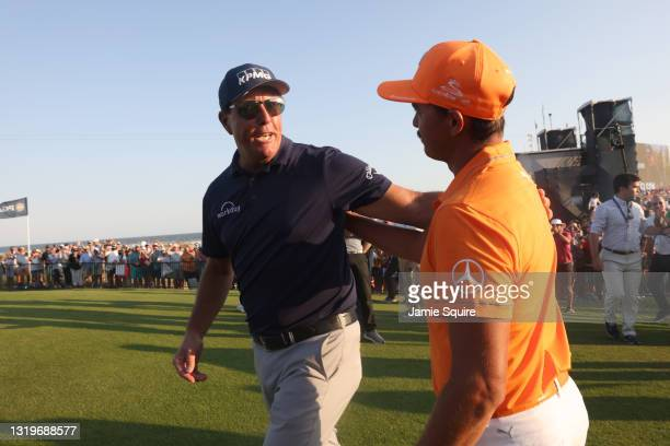 Phil Mickelson of the United States celebrates with Rickie Fowler of the United States after winning on the 18th green during the final round of the...