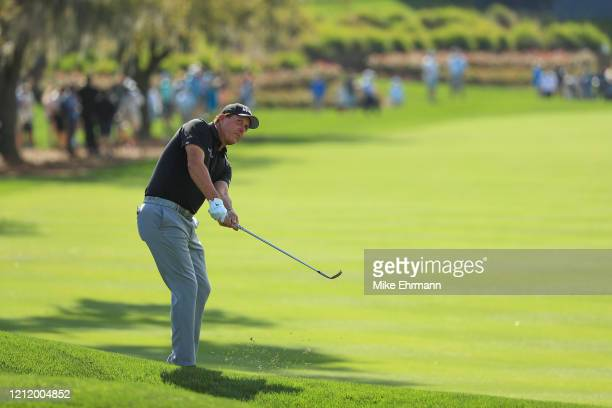 Phil Mickelson of the United States chips to the 18th green during the first round of The PLAYERS Championship on The Stadium Course at TPC Sawgrass...