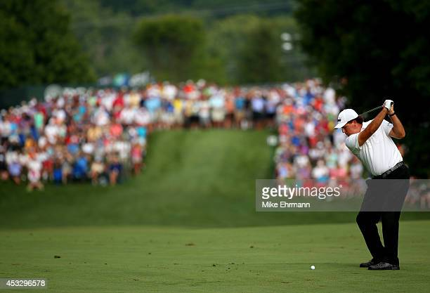 Phil Mickelson of the United States hits an approach shot on the 12th hole during the first round of the 96th PGA Championship at Valhalla Golf Club...