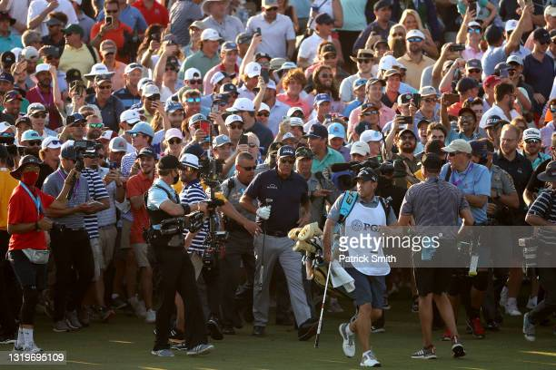 Phil Mickelson of the United States is followed by a crowd of fans as he walks up the 18th fairway during the final round of the 2021 PGA...