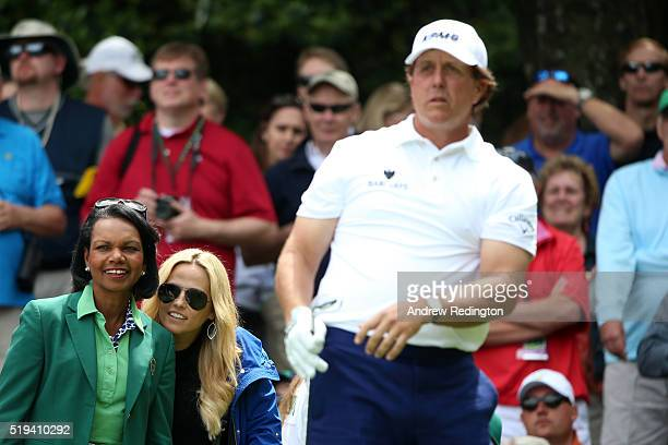 Phil Mickelson of the United States is watched by wife Amy and Former United States Secretary of State Condoleezza Rice during the Par 3 Contest...