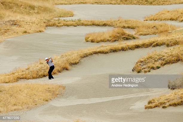 Phil Mickelson of the United States plays a bunker shot on the 14th hole during the first round of the 115th US Open Championship at Chambers Bay on...