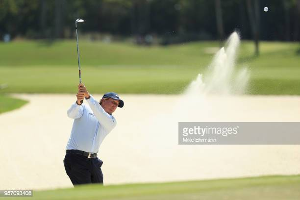 Phil Mickelson of the United States plays a shot from a bunker on the seventh hole during the first round of THE PLAYERS Championship on the Stadium...