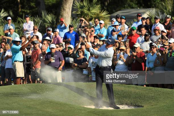 Phil Mickelson of the United States plays a shot from a bunker on the 14th hole during the first round of THE PLAYERS Championship on the Stadium...