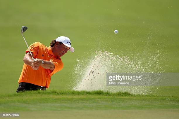 Phil Mickelson of the United States plays a shot out of the bunker on the twelfth hole during the first round of the World Golf ChampionshipsCadillac...