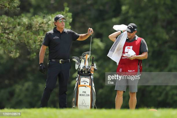 Phil Mickelson of the United States pulls a club from a bag as he prepares to play a shot from the fifth tee during the final round of the Travelers...