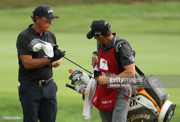 Phil Mickelson of the United States pulls a club from a bag as he prepares to play a shot on the 17th hole during the final round of the Travelers...