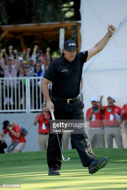 Phil Mickelson of the United States reacts as he holes a crucial birdie putt on the par 4 16th hole during the final round of the World Golf...