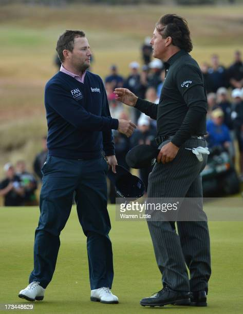 Phil Mickelson of the United States shakes hands with Branden Grace of South Africa on the 18th green after his victory on the 1st hole of a...