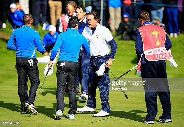 Phil Mickelson of the United States shakes hands with Rory McIlroy of Europe on the 18th green during the Morning Fourballs of the 2014 Ryder Cup on...