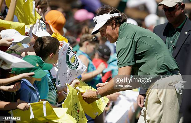 Phil Mickelson of the United States signs autographs during the Par 3 Contest prior to the start of the 2014 Masters Tournament at Augusta National...