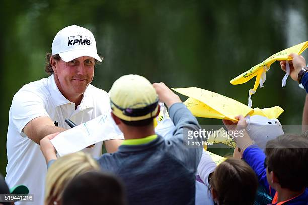 Phil Mickelson of the United States signs autographs during the Par 3 Contest prior to the start of the 2016 Masters Tournament at Augusta National...