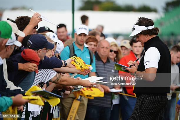 Phil Mickelson of the United States signs his autograph for fans during a practice round prior to the start of The 143rd Open Championship at Royal...