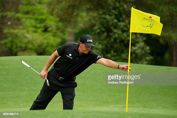 Phil Mickelson of the United States takes the flagstick on the eighth green during the final round of the 2015 Masters Tournament at Augusta National...