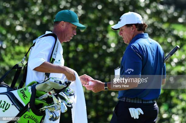 Phil Mickelson of the United States talks with caddie Jim 'Bones' Mackay on the tenth green during a practice round prior to the start of the 2017...