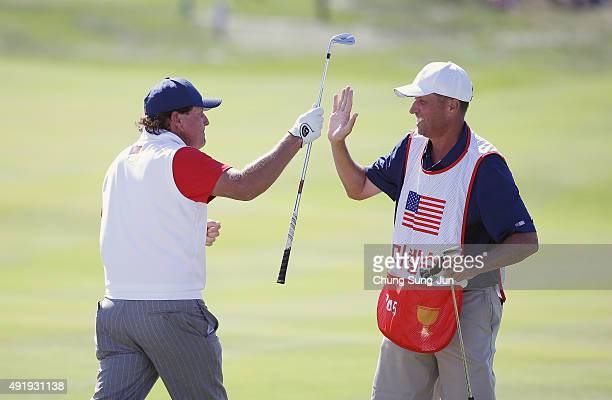 Phil Mickelson of the United States Team celebrates with his caddie Jim Mackay after holing a bunker shot on the 12th hole during the Friday...