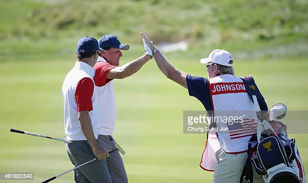 Phil Mickelson of the United States Team celebrates with Zach Johnson and Johnson's caddie Damon Green after holing a bunker shot on the 12th hole...